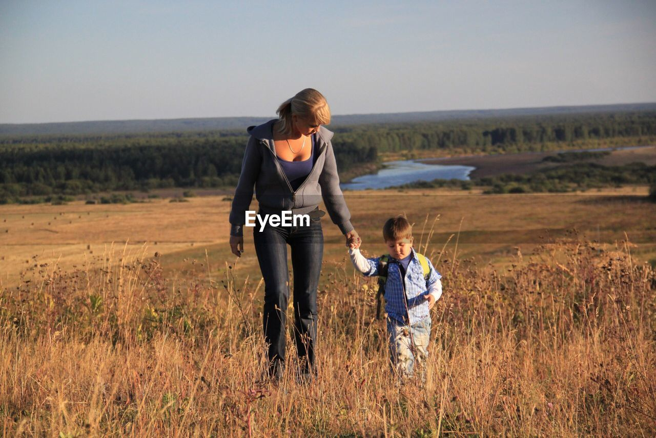 Mother with son walking on grassy field against clear sky
