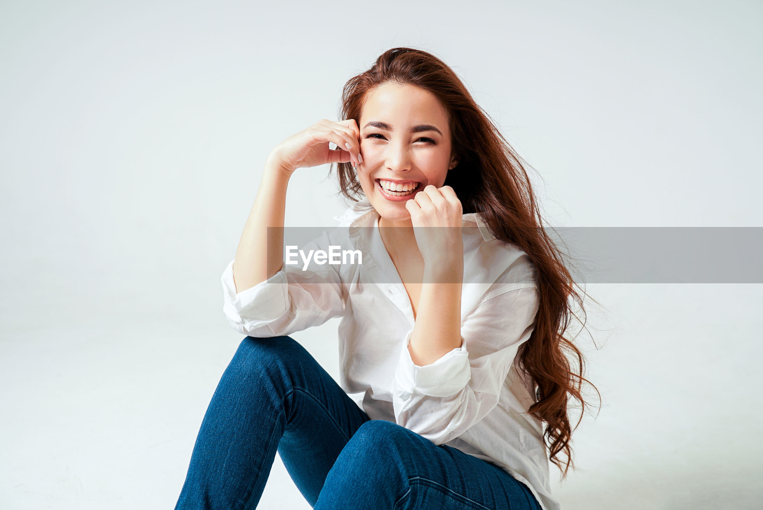 Portrait of smiling young woman sitting against white background