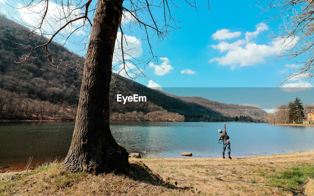 water, lake, nature, real people, tree, one person, leisure activity, full length, beauty in nature, tree trunk, sky, day, standing, outdoors, scenics, men, lifestyles