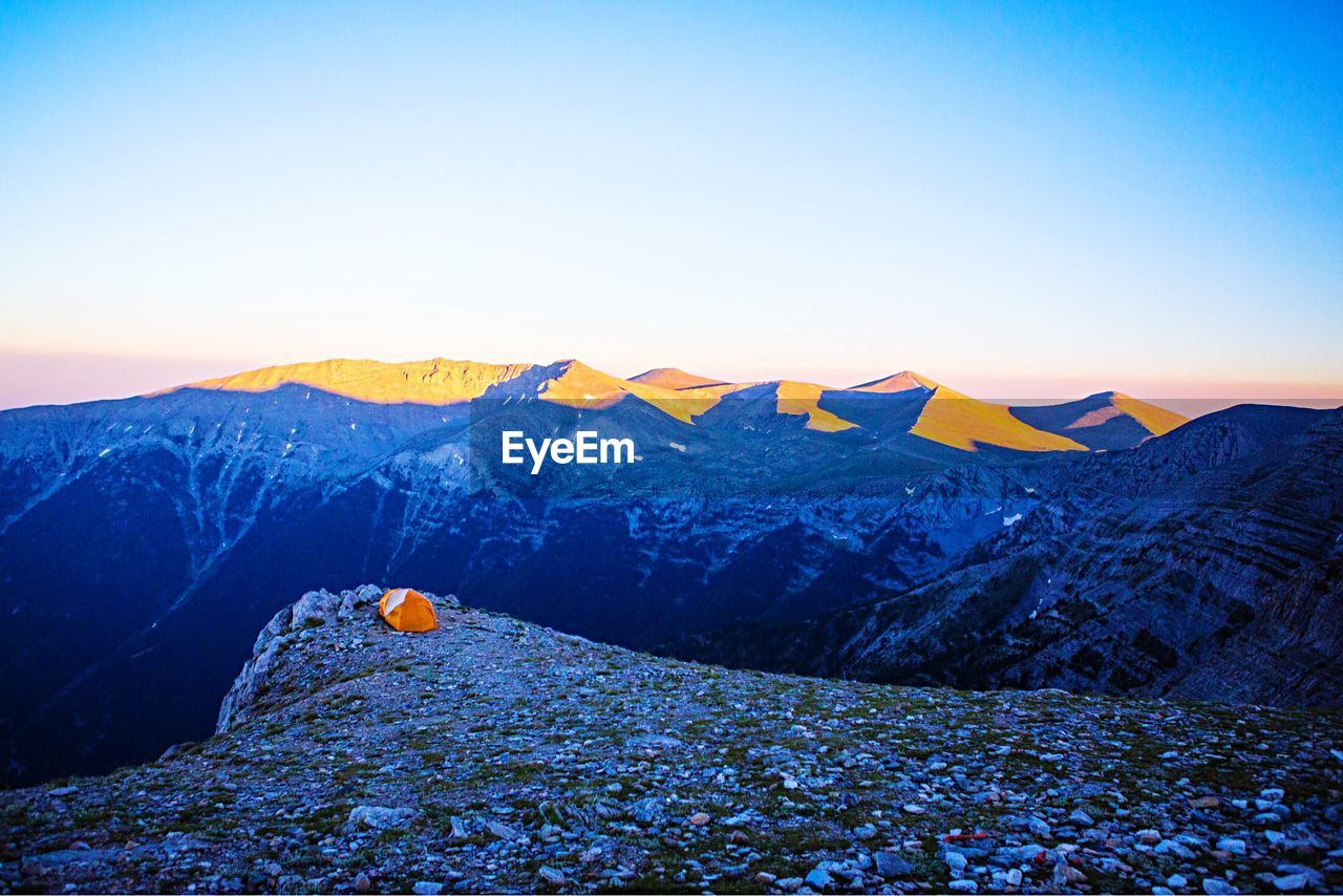 mountain, beauty in nature, tranquil scene, sky, tranquility, scenics - nature, non-urban scene, nature, environment, landscape, idyllic, no people, clear sky, mountain range, remote, blue, snow, sunset, copy space, outdoors, snowcapped mountain, mountain peak, formation