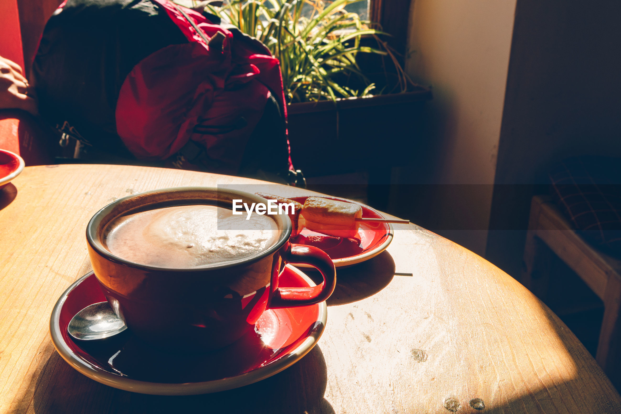 HIGH ANGLE VIEW OF COFFEE CUP ON TABLE AT CAFE