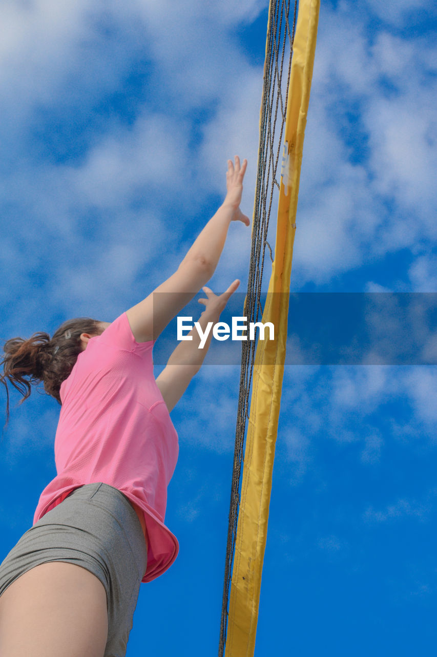 Low angle view of woman reaching volleyball net
