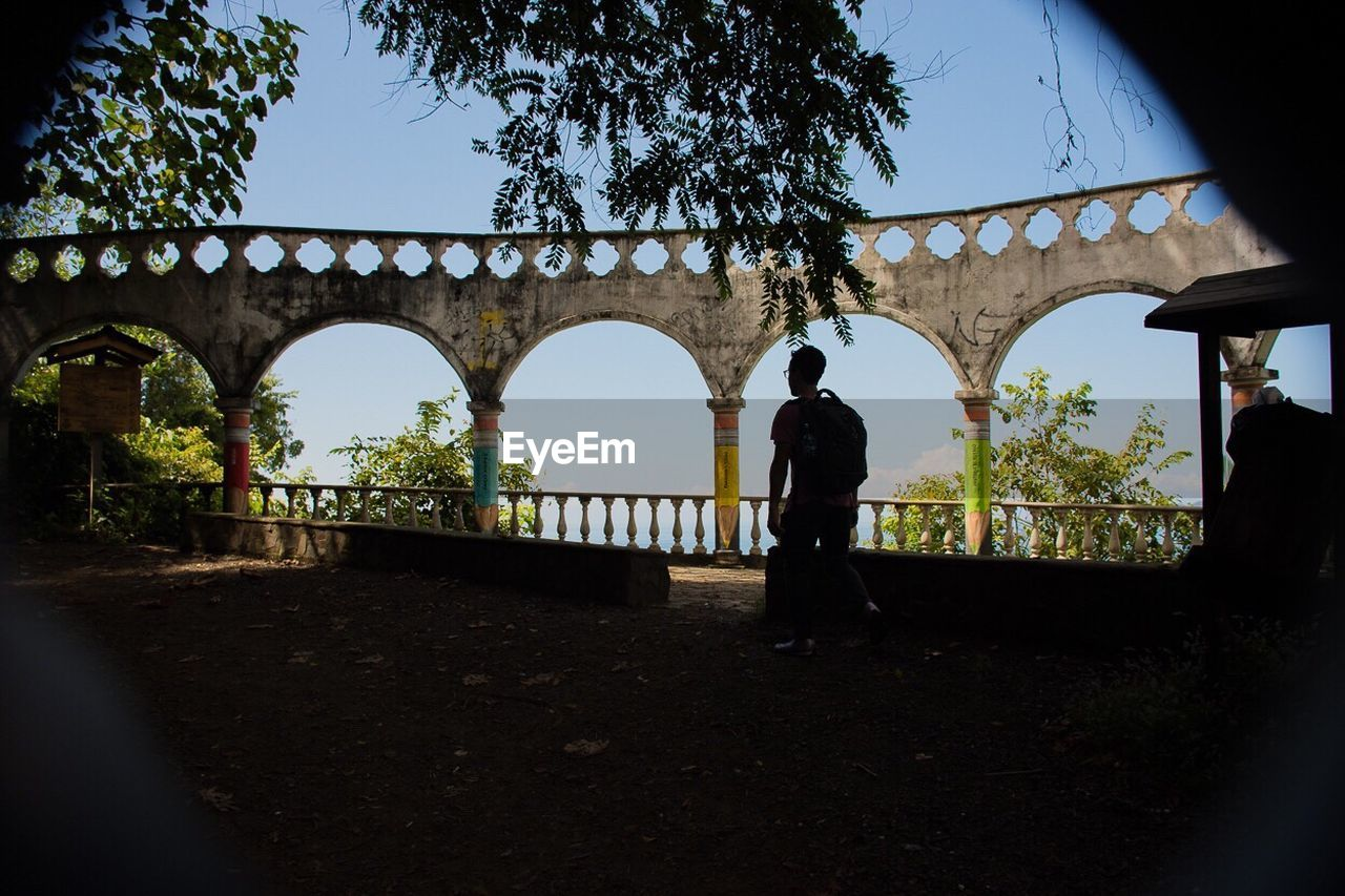 arch, real people, architecture, built structure, tree, bridge - man made structure, silhouette, walking, full length, day, standing, men, women, outdoors, lifestyles, one person, clear sky, nature, sky, people
