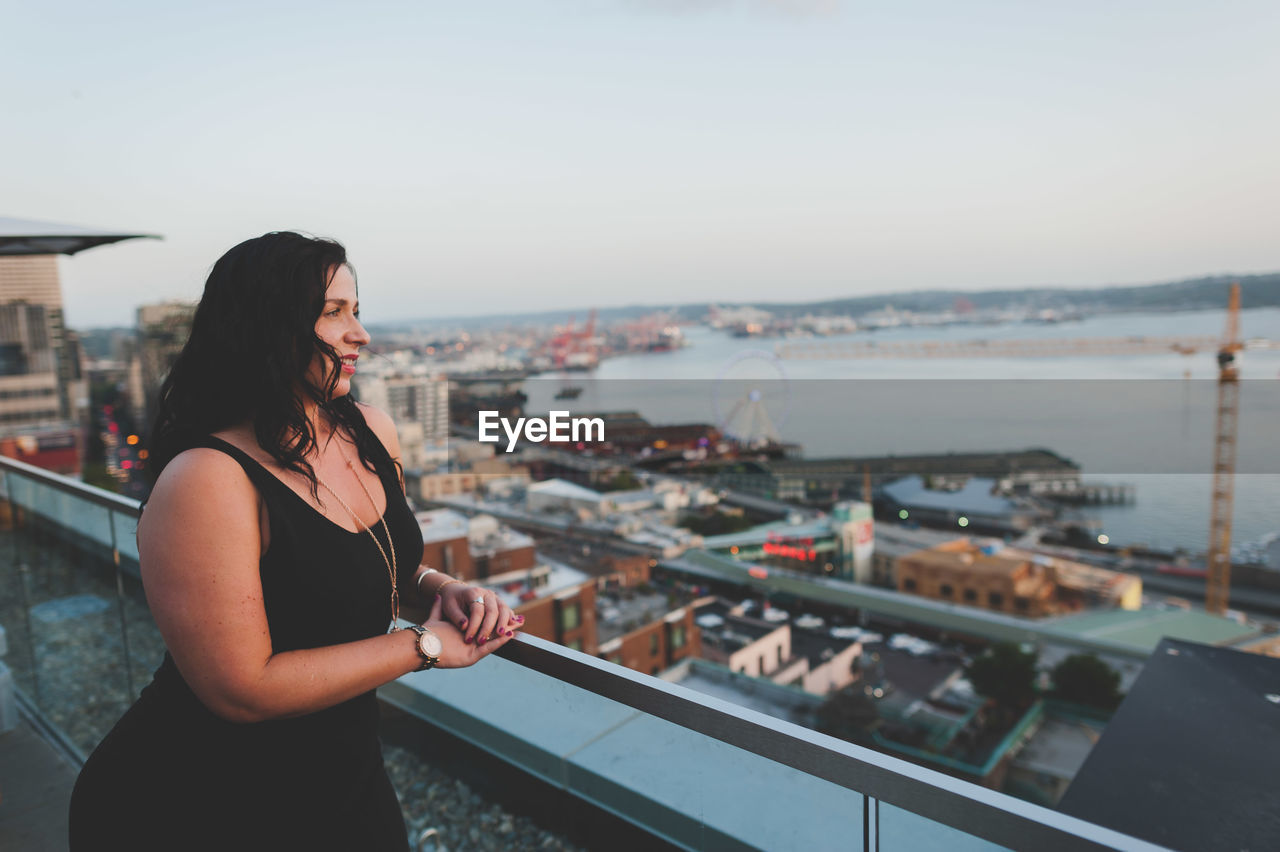 Beautiful Woman Leaning On Railing Against Sky