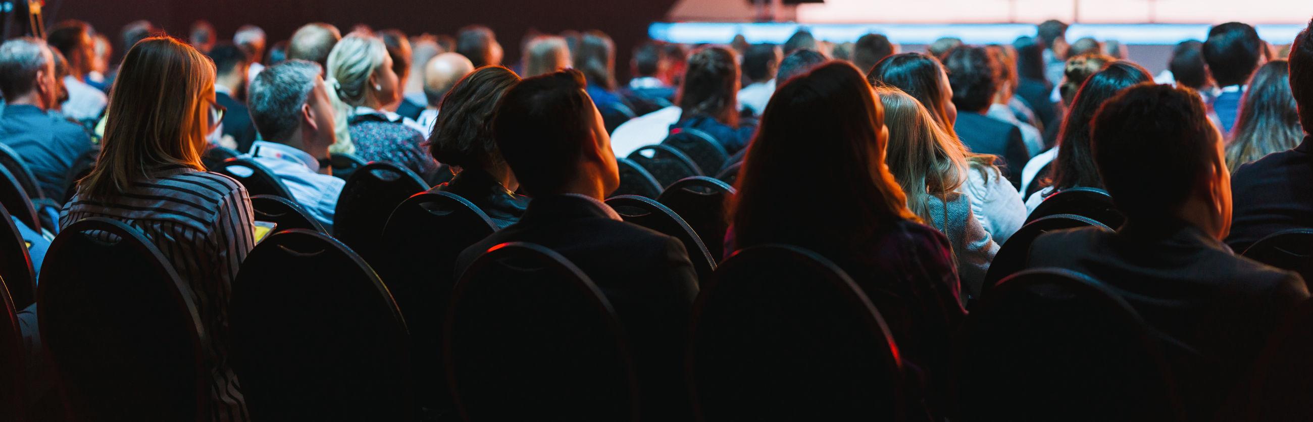 Rear view of people sitting in auditorium during seminar