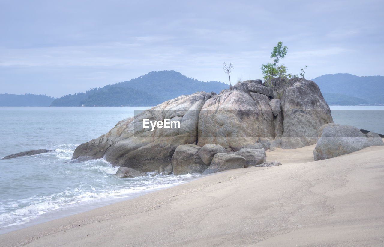 sea, water, sky, land, beach, rock, beauty in nature, nature, scenics - nature, sand, rock - object, motion, no people, solid, tranquility, mountain, day, tranquil scene, outdoors