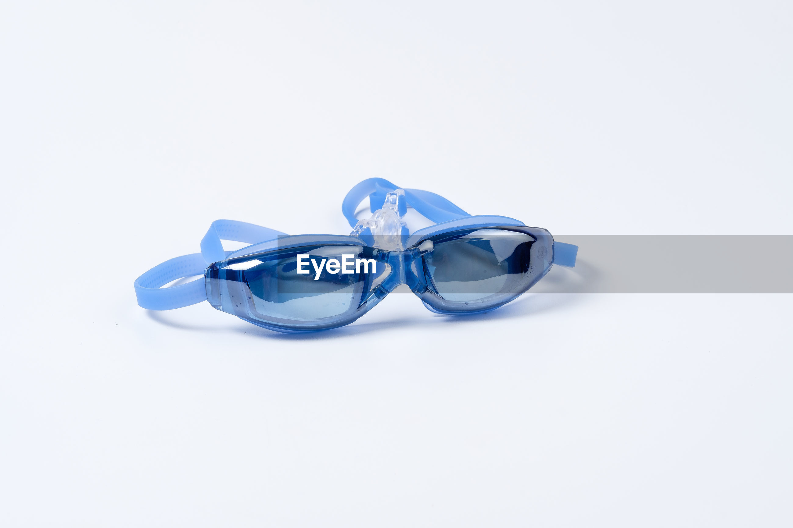 Close-up of swimming goggles over white background