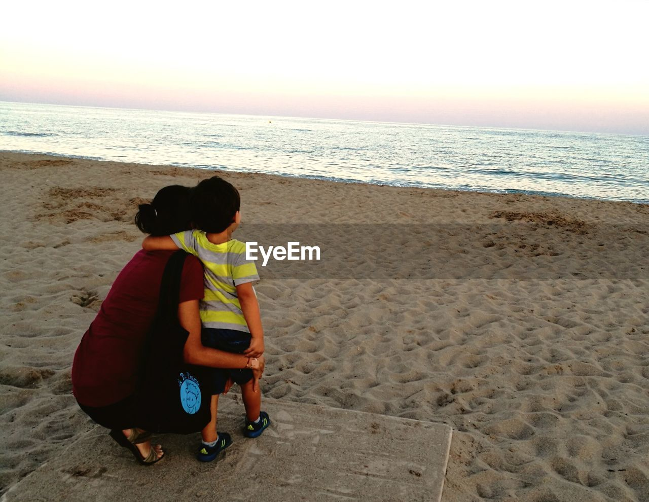 sea, beach, real people, horizon over water, rear view, full length, sand, childhood, togetherness, leisure activity, boys, vacations, love, lifestyles, nature, family with one child, beauty in nature, water, scenics, bonding, day, women, clear sky, sitting, outdoors, sky, standing, people