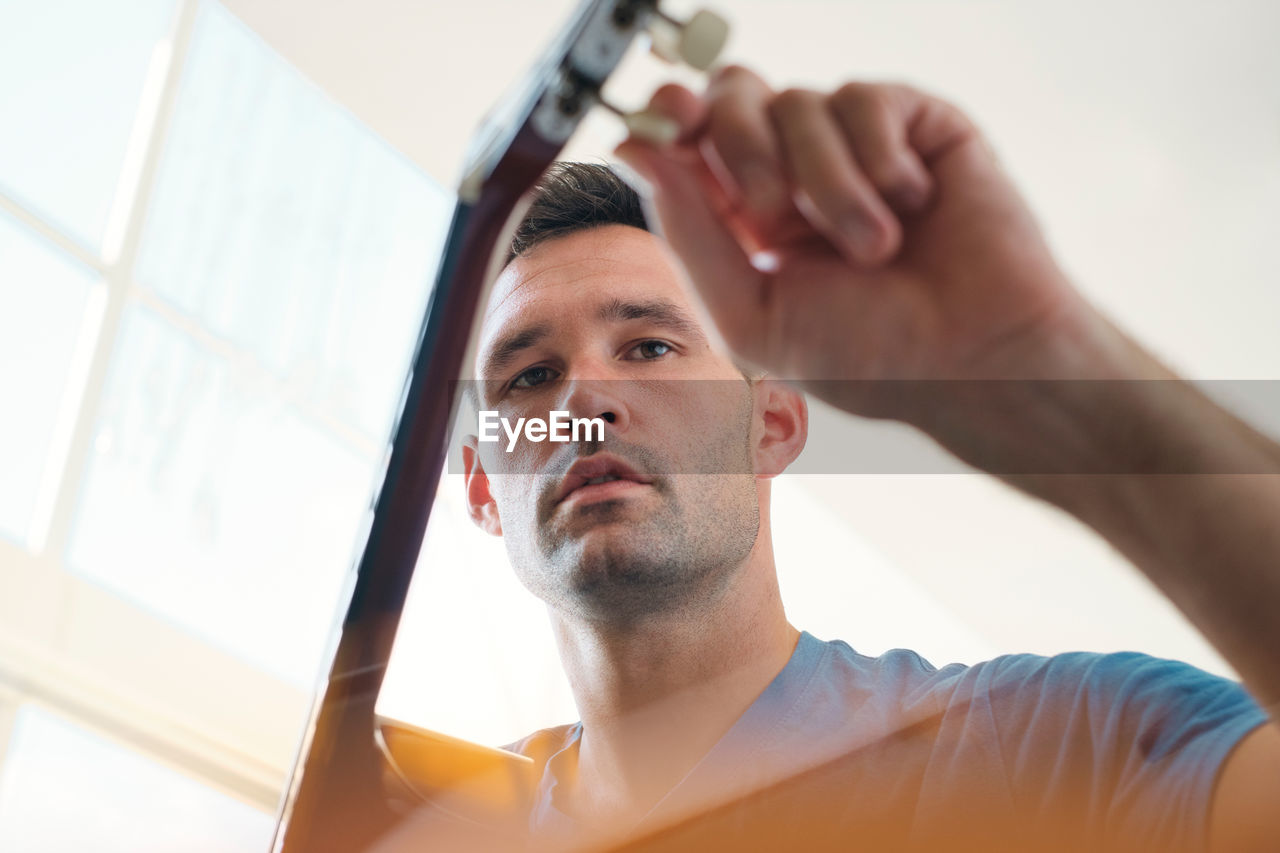 Low angle view of man holding guitar sitting at home