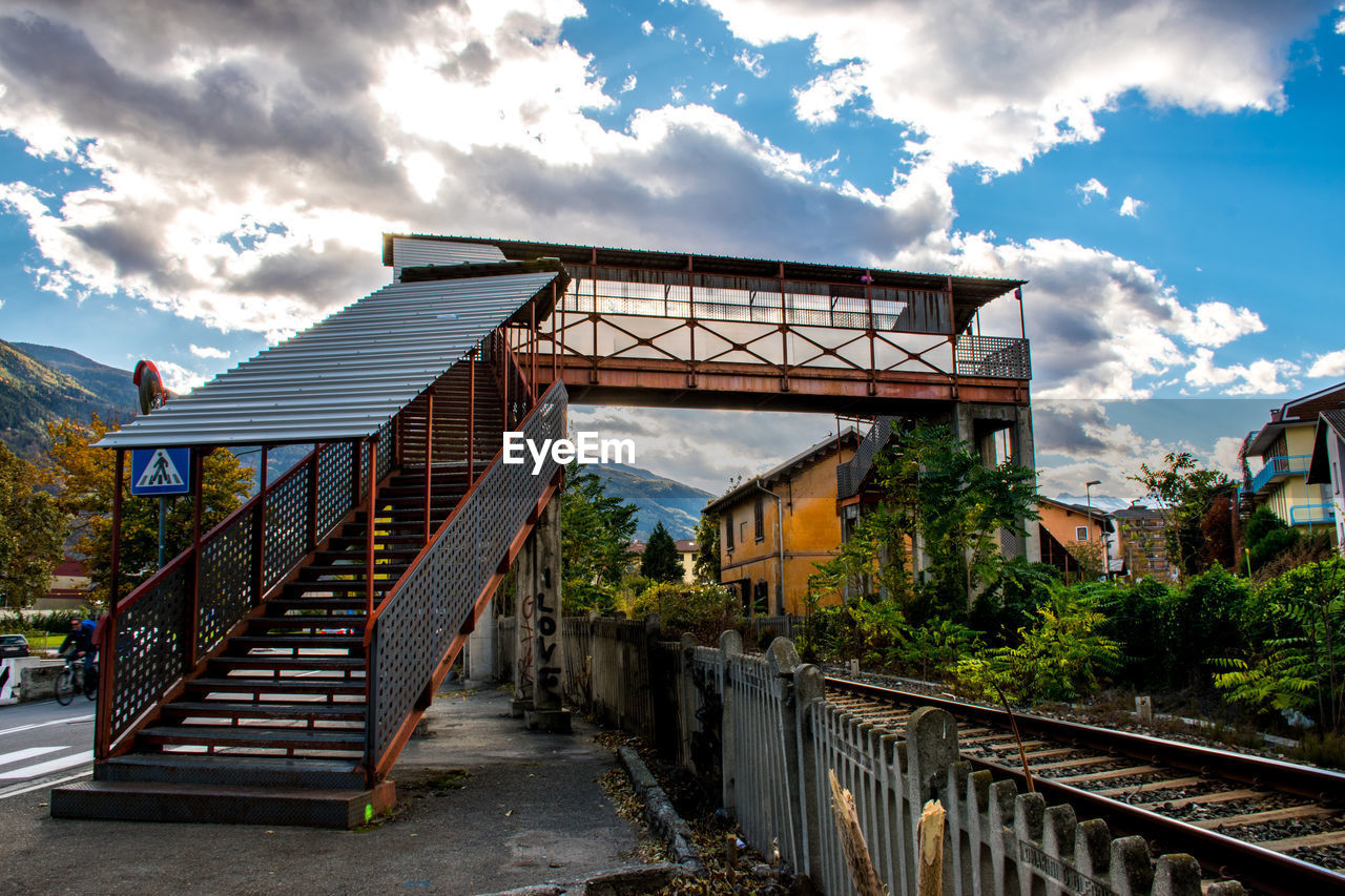 architecture, built structure, cloud - sky, sky, building exterior, railing, nature, plant, no people, tree, day, connection, bridge, building, staircase, the way forward, direction, transportation, city, outdoors
