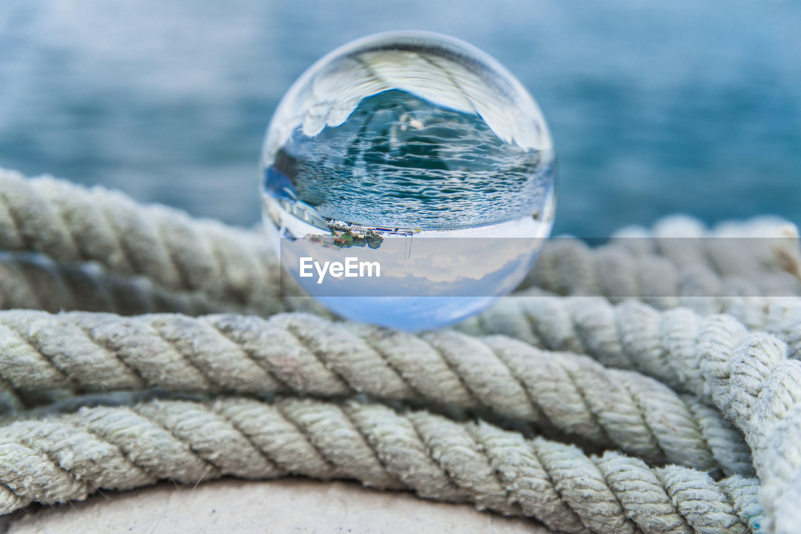 Close-up of crystal ball on rope at harbor
