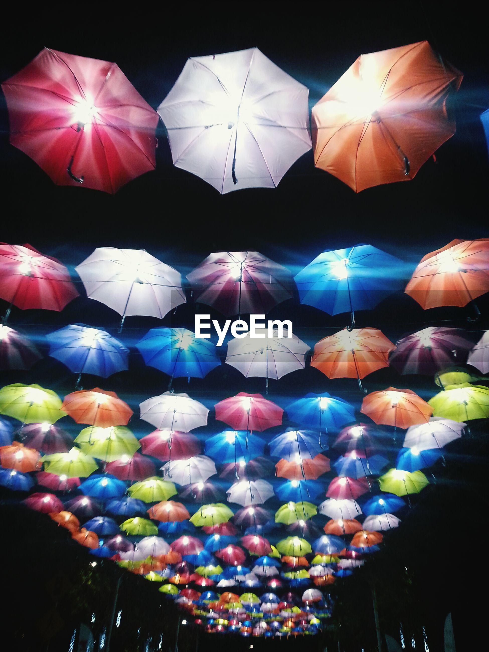 Illuminated multi colored umbrellas hanging from ceiling