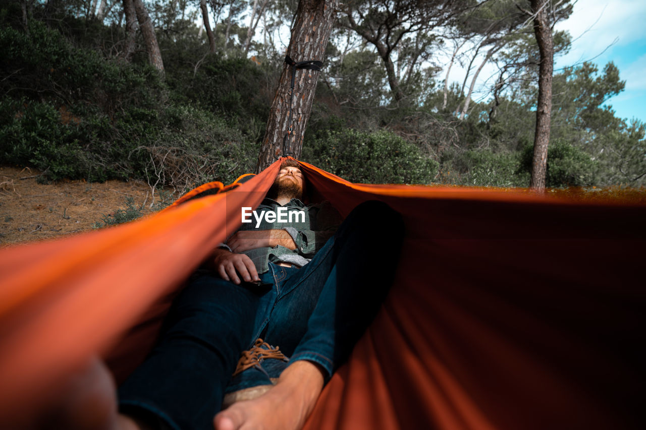 Full length of man sleeping in hammock in forest
