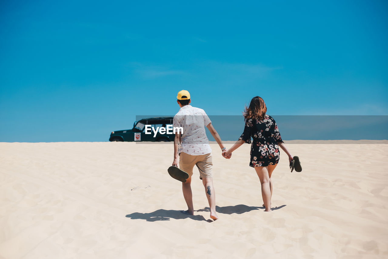 rear view, two people, real people, land, sky, lifestyles, full length, nature, leisure activity, sunlight, sand, women, togetherness, walking, adult, people, beach, blue, shadow, day, couple - relationship, outdoors