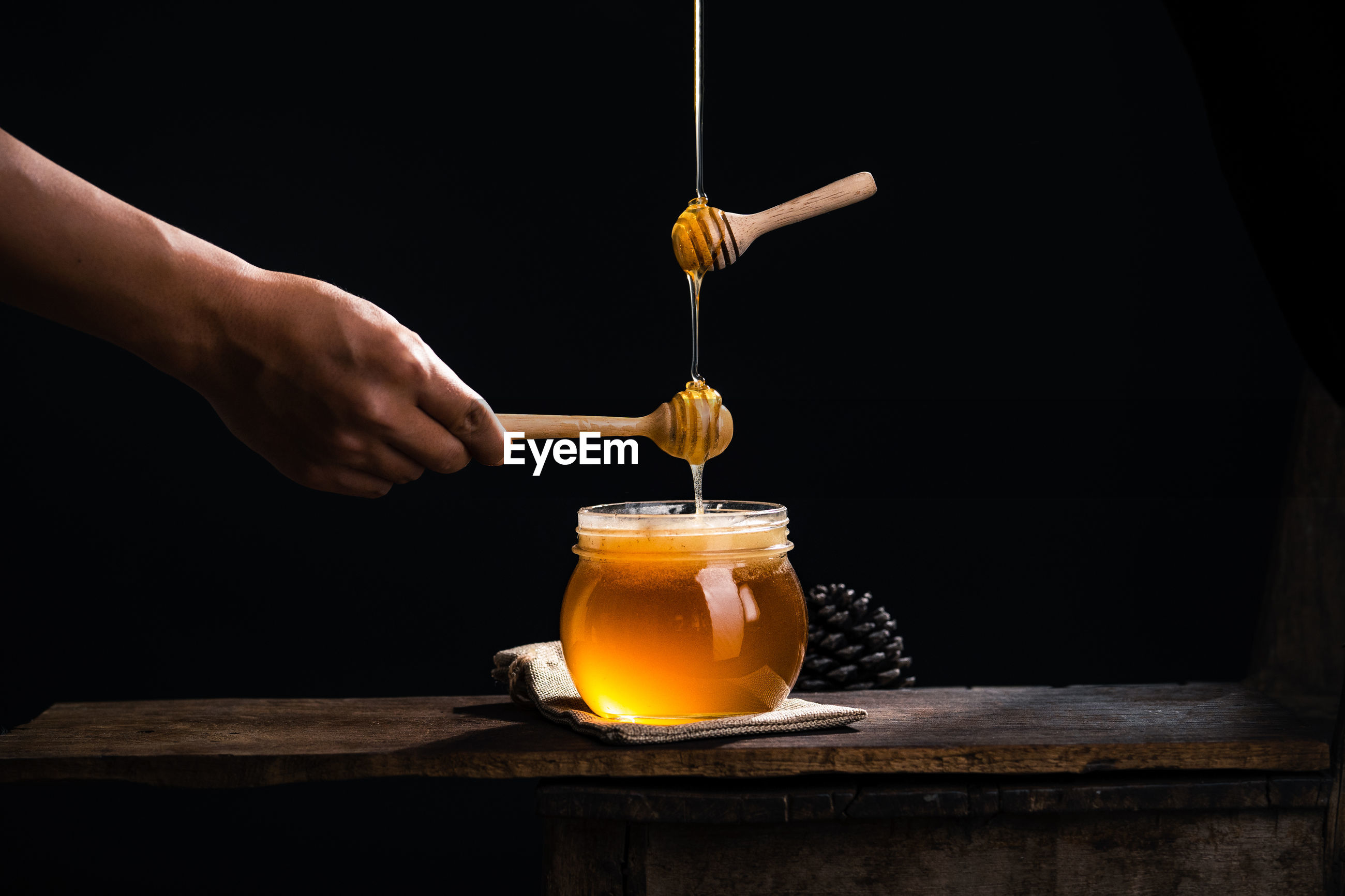 Hand holding drink on table against black background