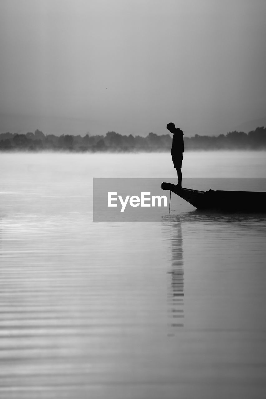 Silhouette man standing in rowboat on lake at dusk