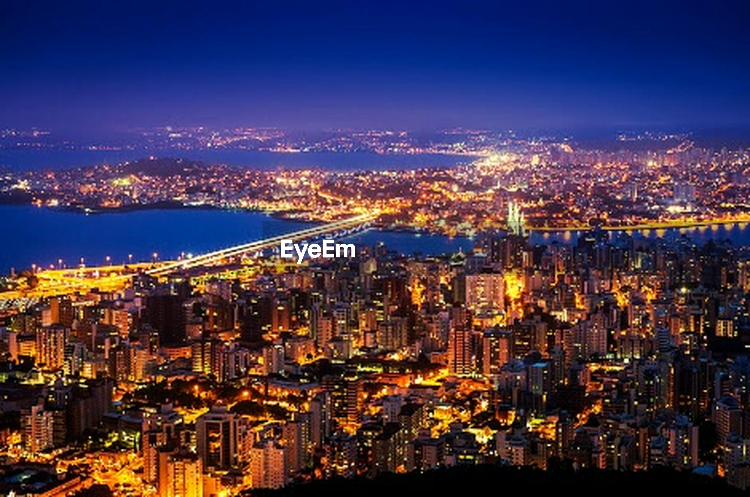 cityscape, city, illuminated, night, architecture, building exterior, built structure, crowded, skyscraper, high angle view, modern, city life, river, capital cities, water, residential district, tower, aerial view, sky, office building
