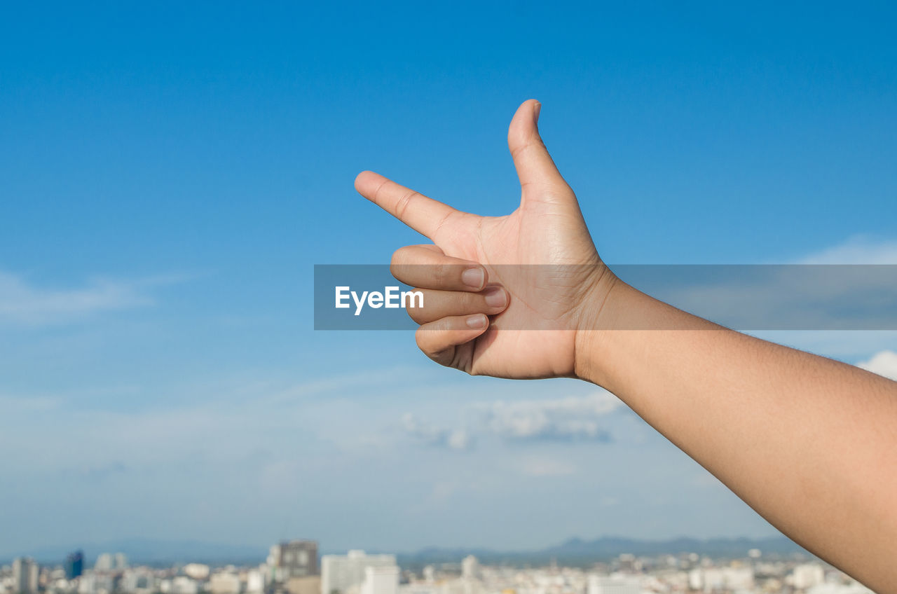 Cropped human hand pointing against sky
