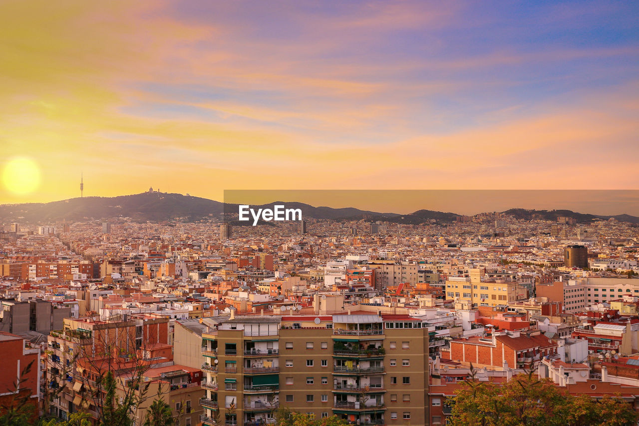 architecture, building exterior, built structure, city, cityscape, building, residential district, sky, crowd, crowded, nature, sunset, cloud - sky, community, outdoors, high angle view, orange color, town, house, townscape, apartment, settlement, romantic sky