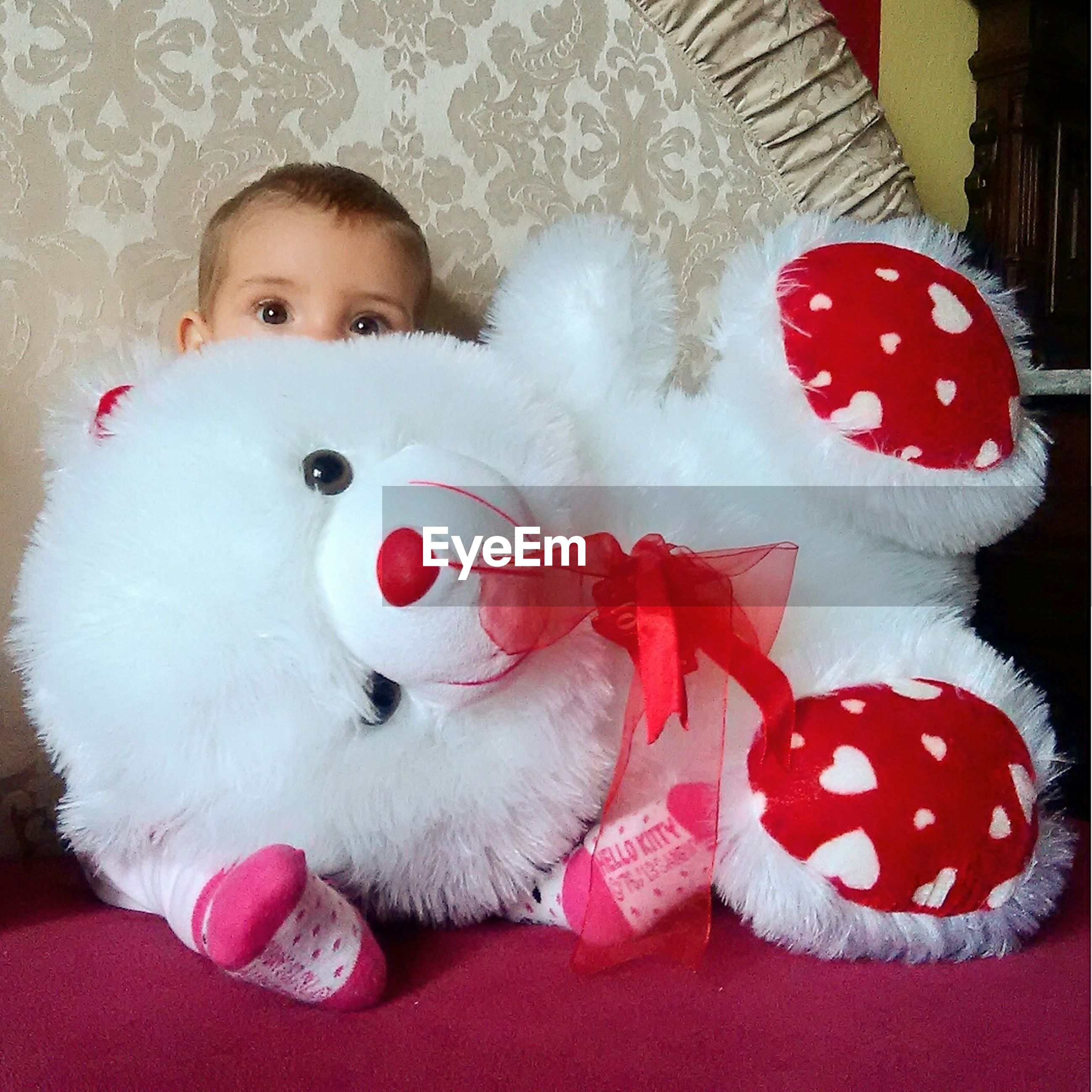 Portrait of baby girl sitting on floor with stuffed toy