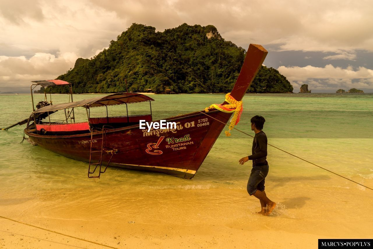 transportation, sea, water, nautical vessel, mode of transport, nature, sky, scenics, beach, longtail boat, beauty in nature, men, moored, cloud - sky, outdoors, horizon over water, day, sand, real people, full length, occupation, one person, people