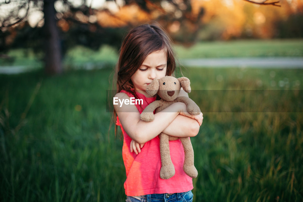 Girl holding stuffed toy and standing on field