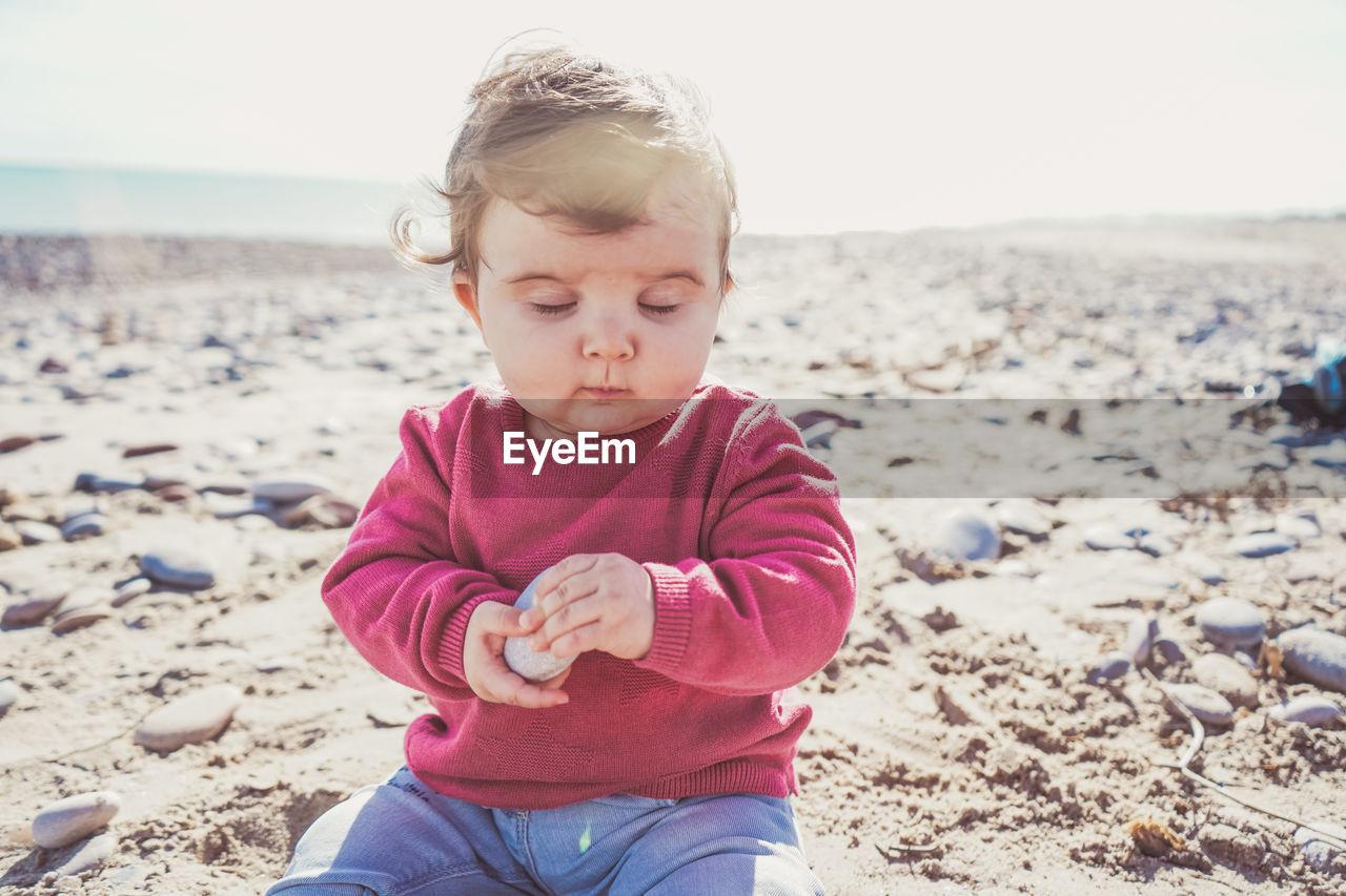Cute girl sitting on sand at beach