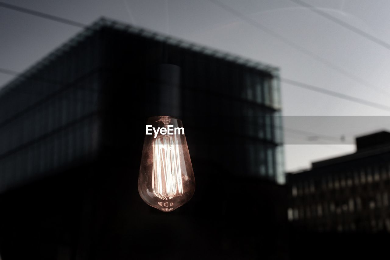 lighting equipment, no people, electricity, illuminated, built structure, architecture, fuel and power generation, light bulb, focus on foreground, light, low angle view, close-up, building exterior, building, outdoors, selective focus, cable, metal, nature, hanging, electric lamp