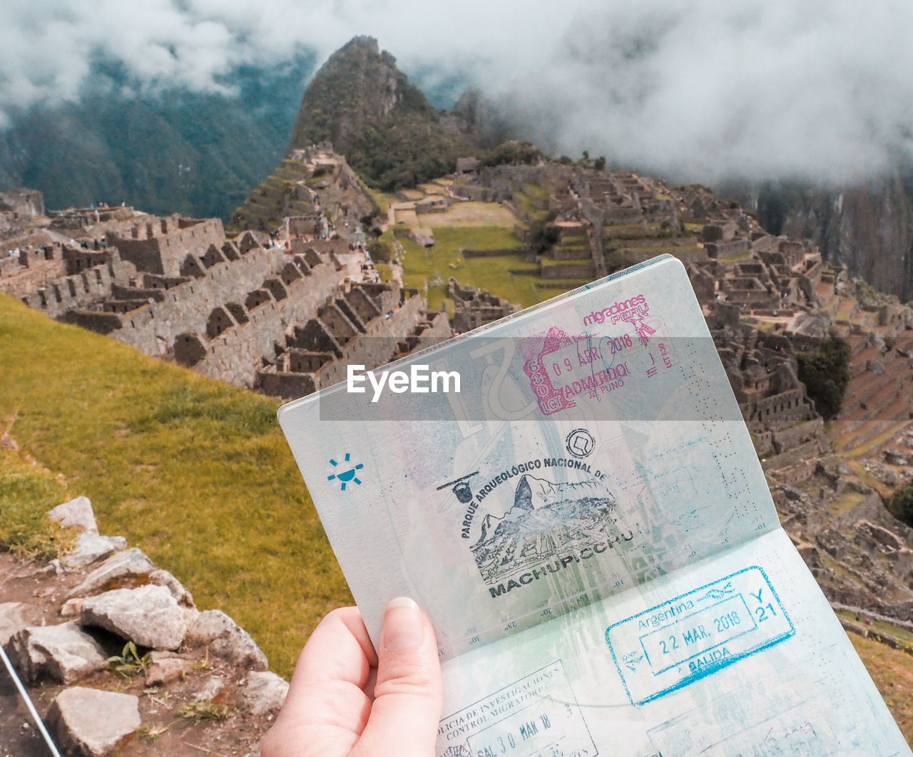 Cropped hand holding passport against machu picchu