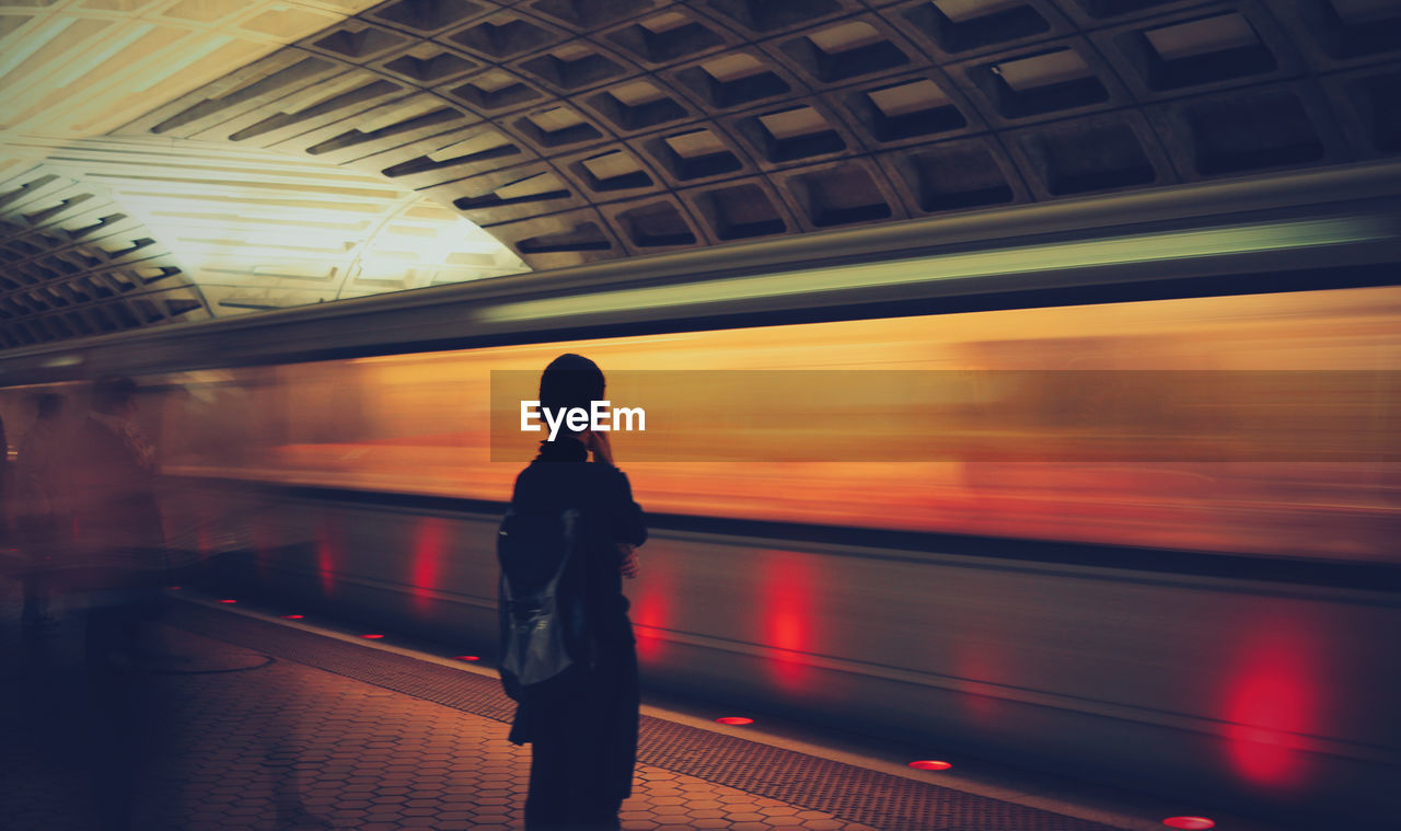 transportation, train - vehicle, public transportation, railroad station, railroad station platform, passenger train, rail transportation, blurred motion, mode of transport, real people, travel, speed, indoors, journey, waiting, subway train, motion, standing, full length, illuminated, women, one person, day, people