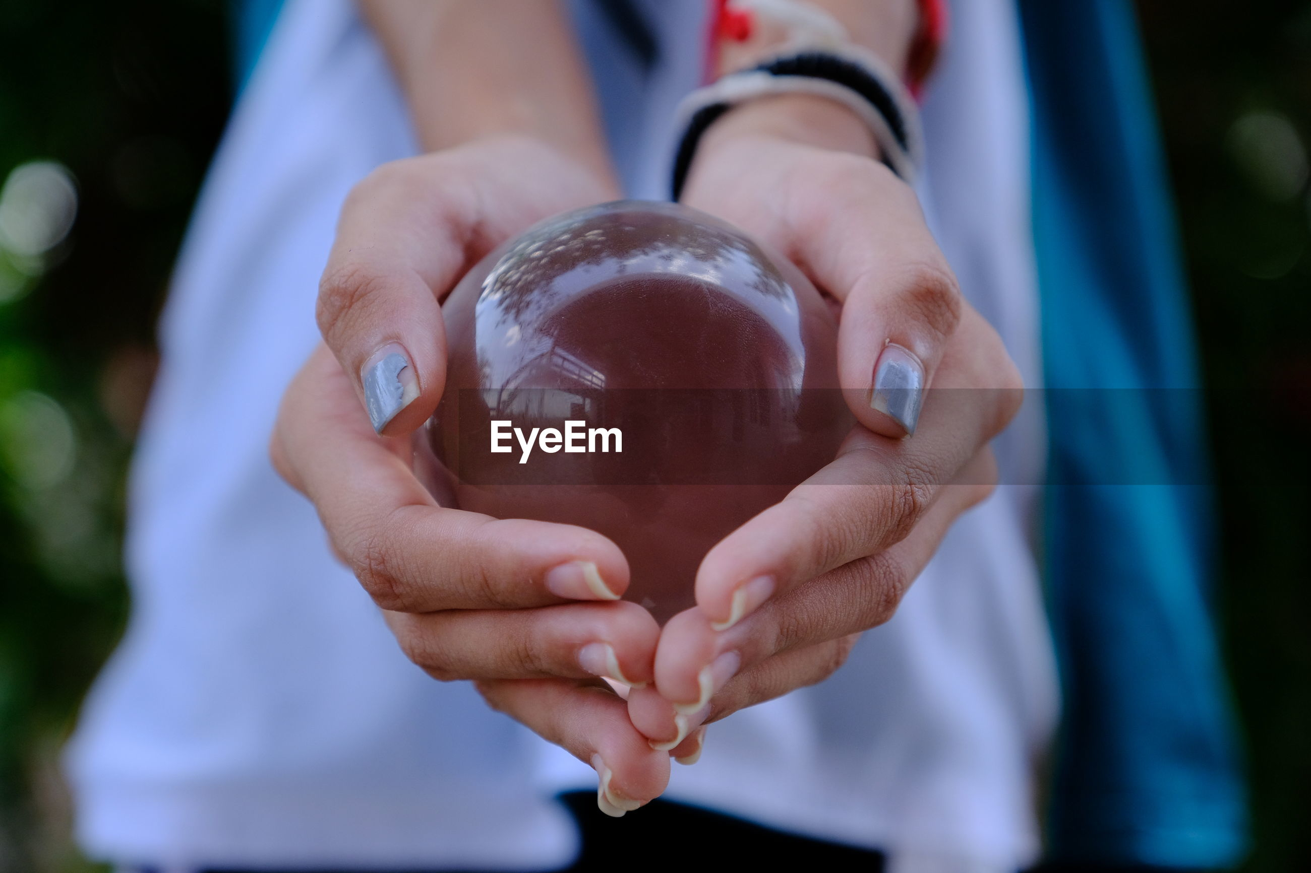 Midsection of woman hand holding crystal ball