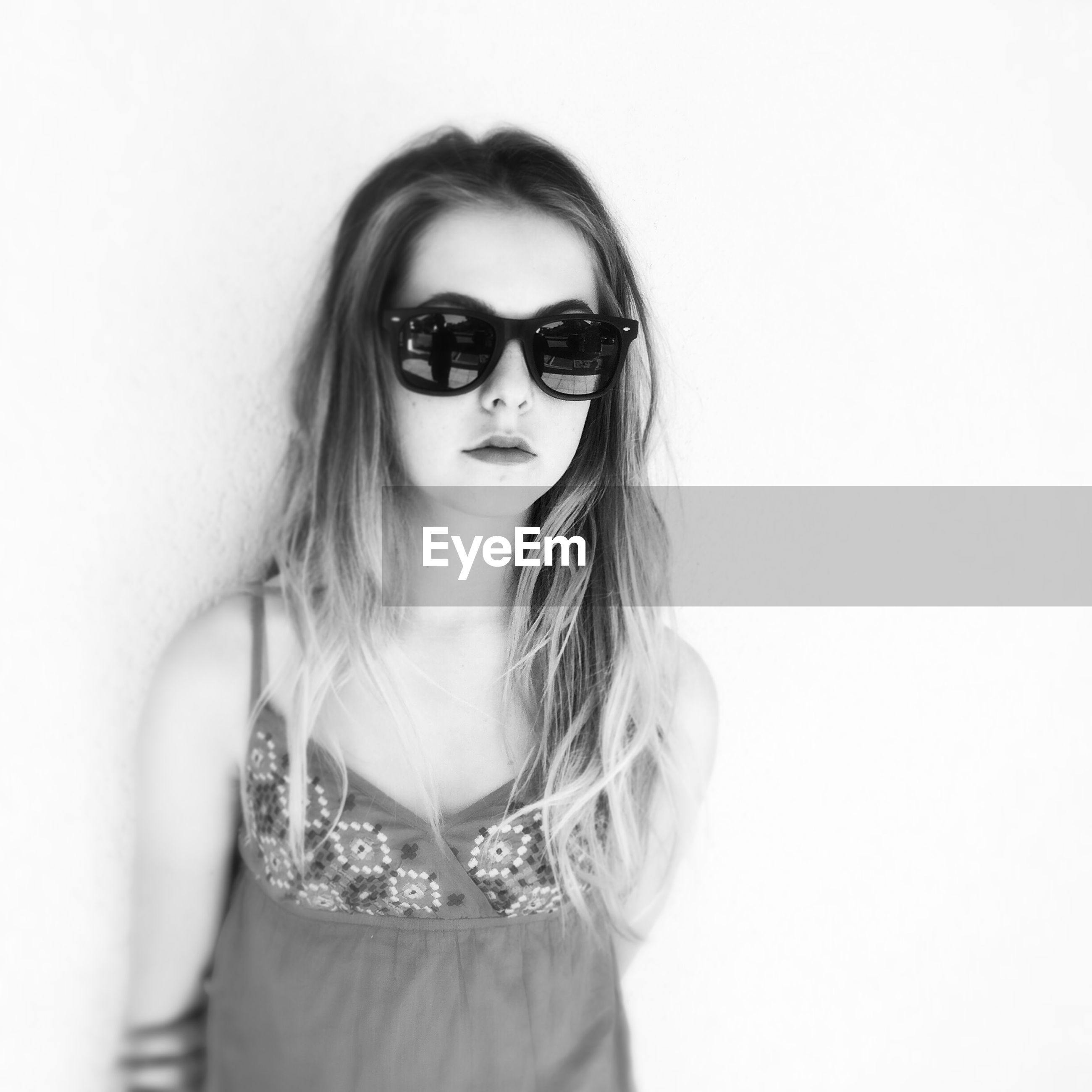 Portrait of young woman in sunglasses against wall