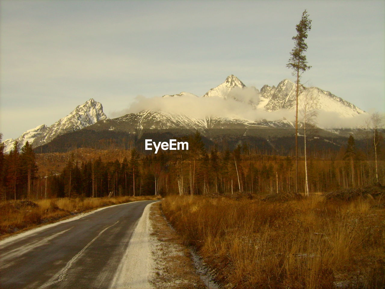 Empty Road Leading Towards Snow Covered Mountains Against Sky