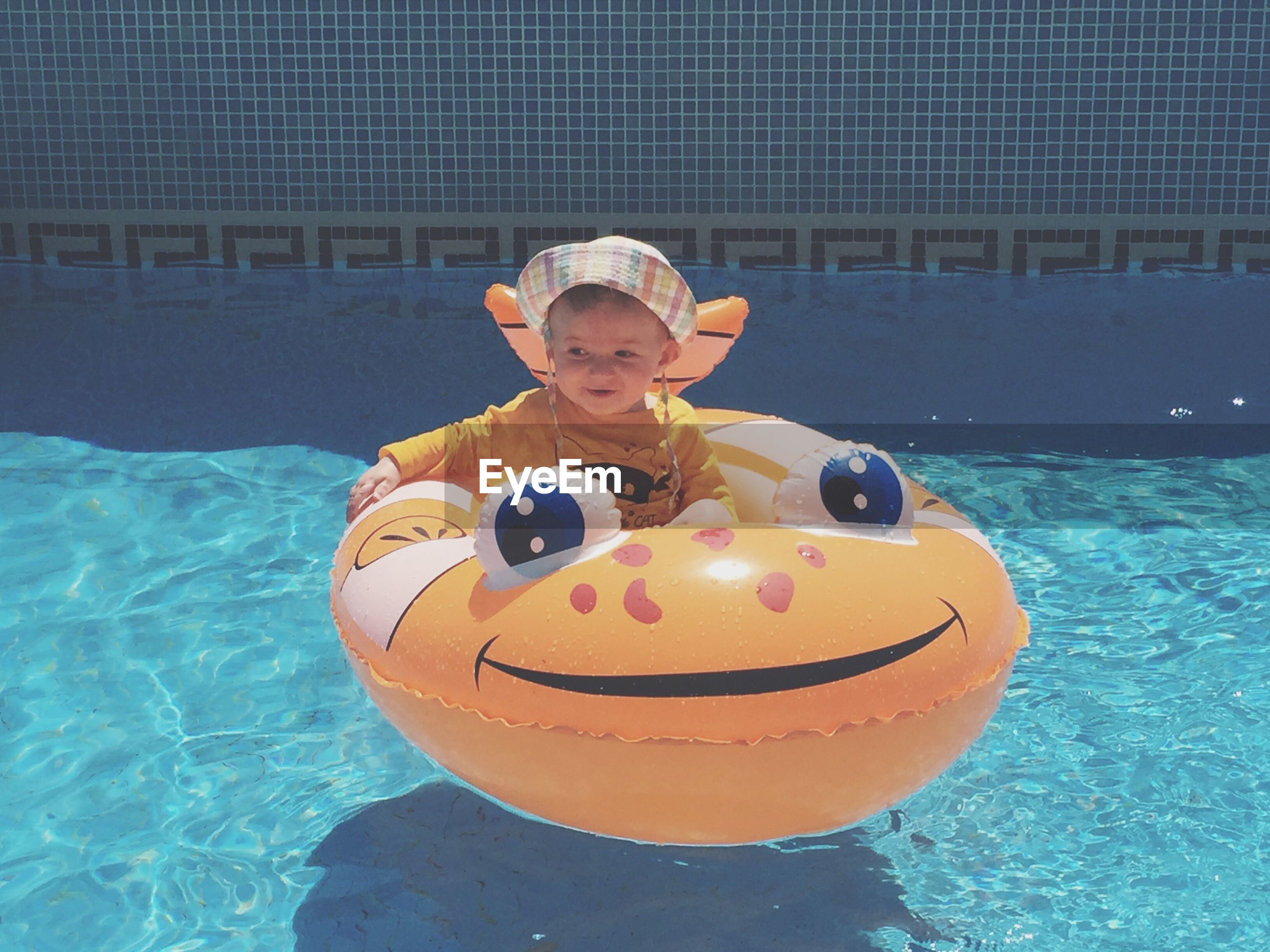 Baby boy on inflatable ring in swimming pool