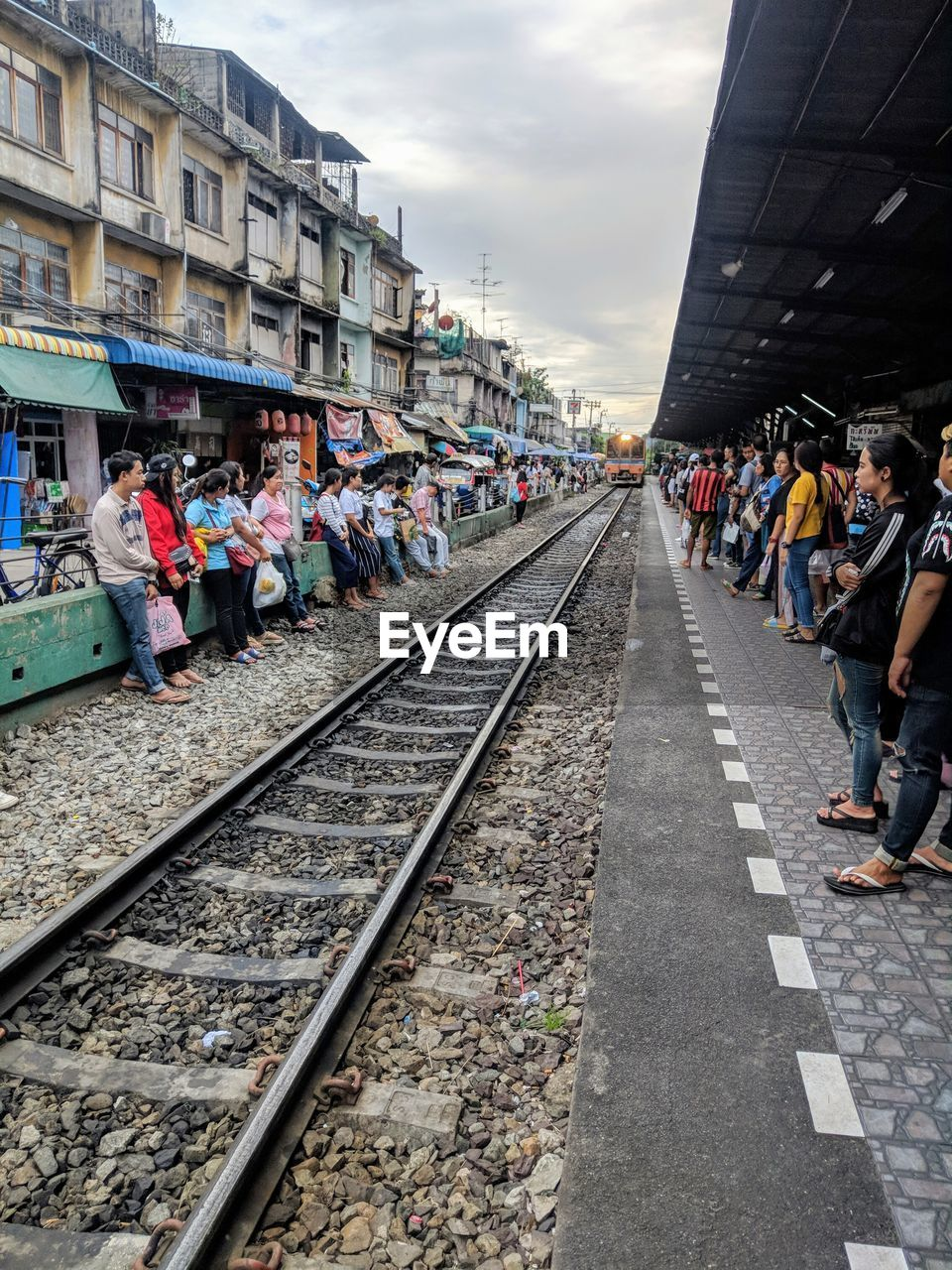 group of people, track, transportation, rail transportation, architecture, large group of people, railroad track, real people, crowd, women, sky, adult, men, day, built structure, building exterior, cloud - sky, lifestyles, nature, outdoors, waiting