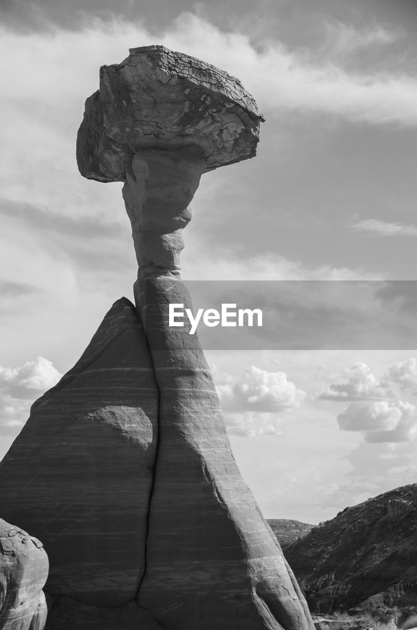 cloud - sky, sky, no people, day, nature, beauty in nature, tranquility, tranquil scene, solid, rock, scenics - nature, rock - object, non-urban scene, focus on foreground, outdoors, travel destinations, rock formation, low angle view, environment, geology, eroded