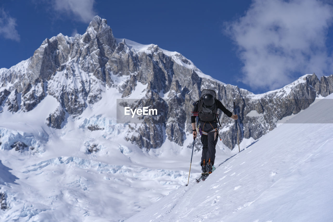 Scenic view of man skiing against mountain range and sky