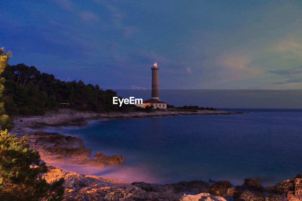LIGHTHOUSE AMIDST SEA AGAINST SKY AT SUNSET