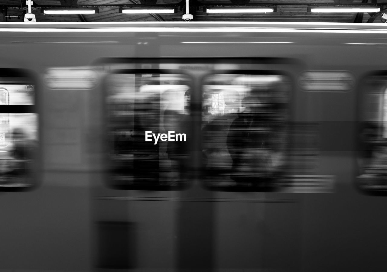 blurred motion, motion, public transportation, rail transportation, mode of transportation, train, transportation, train - vehicle, land vehicle, speed, travel, railroad station, group of people, outdoors, journey, architecture, on the move, subway train, arrival