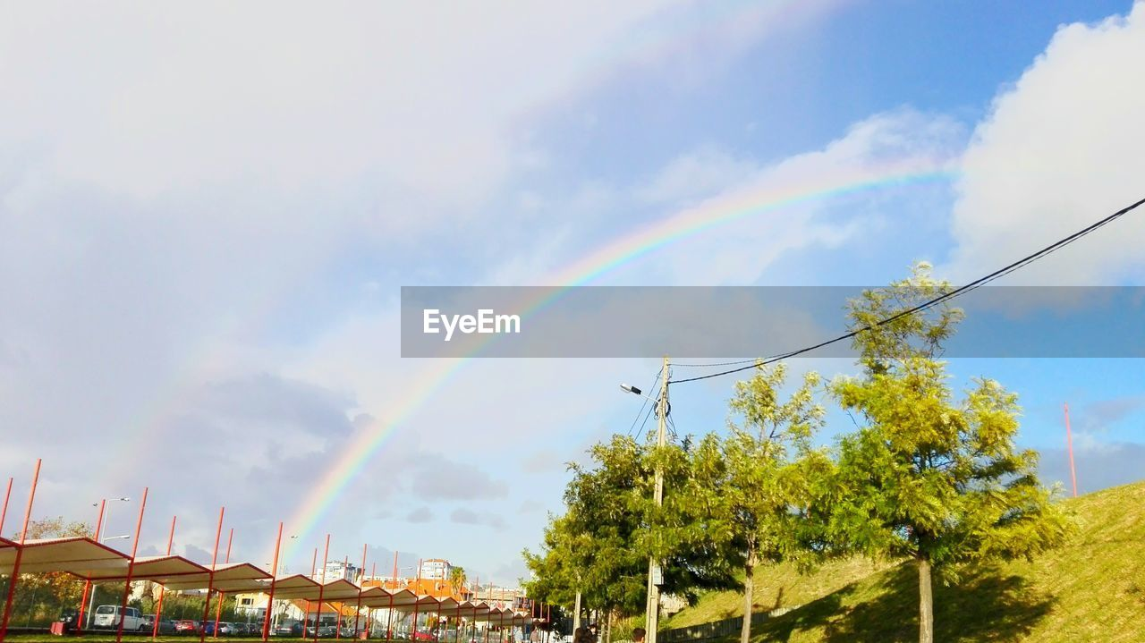 sky, day, rainbow, cloud - sky, low angle view, outdoors, no people, tree, nature, built structure, beauty in nature, multi colored, architecture