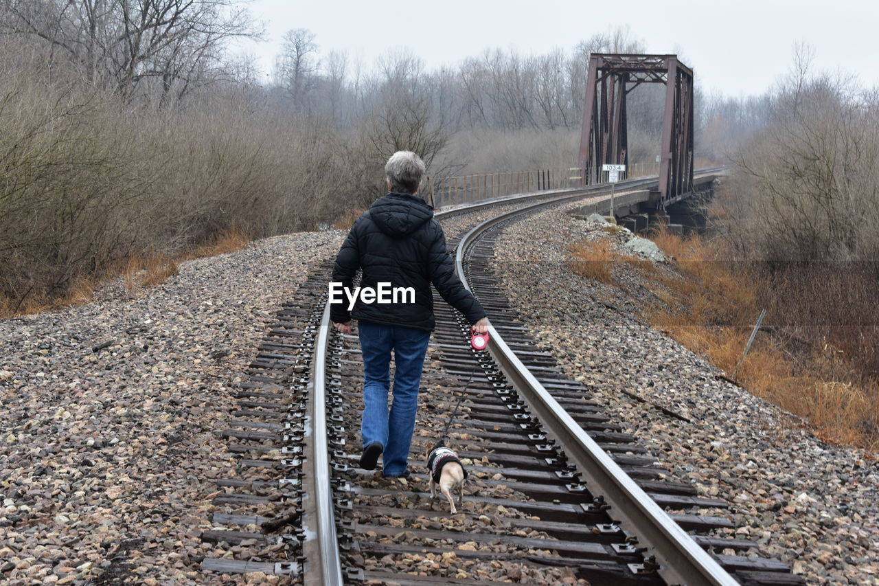Rear View Of Woman With Dog Walking On Railway Tracks In Winter