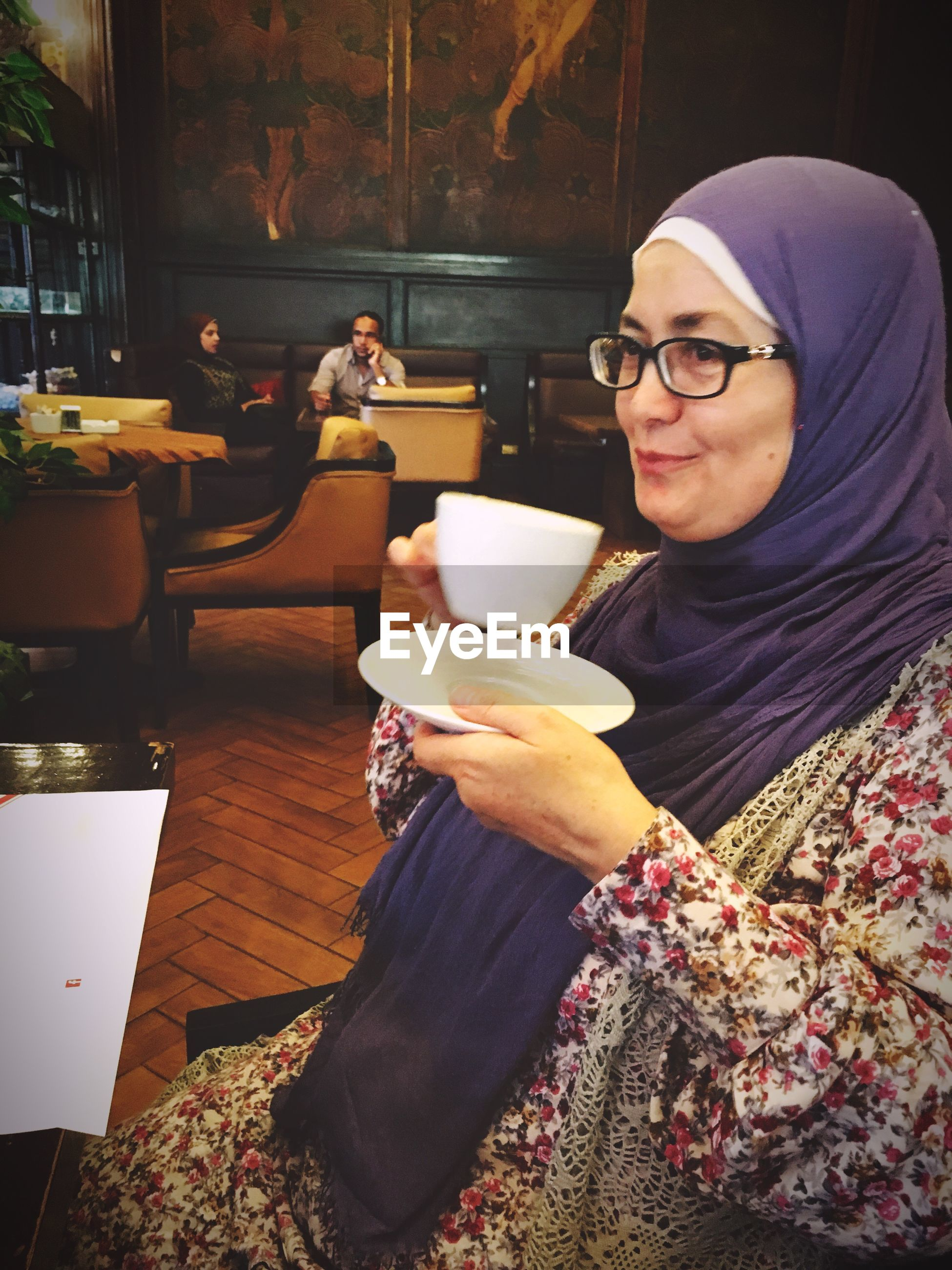 Mid adult woman wearing hijab holding tea in restaurant