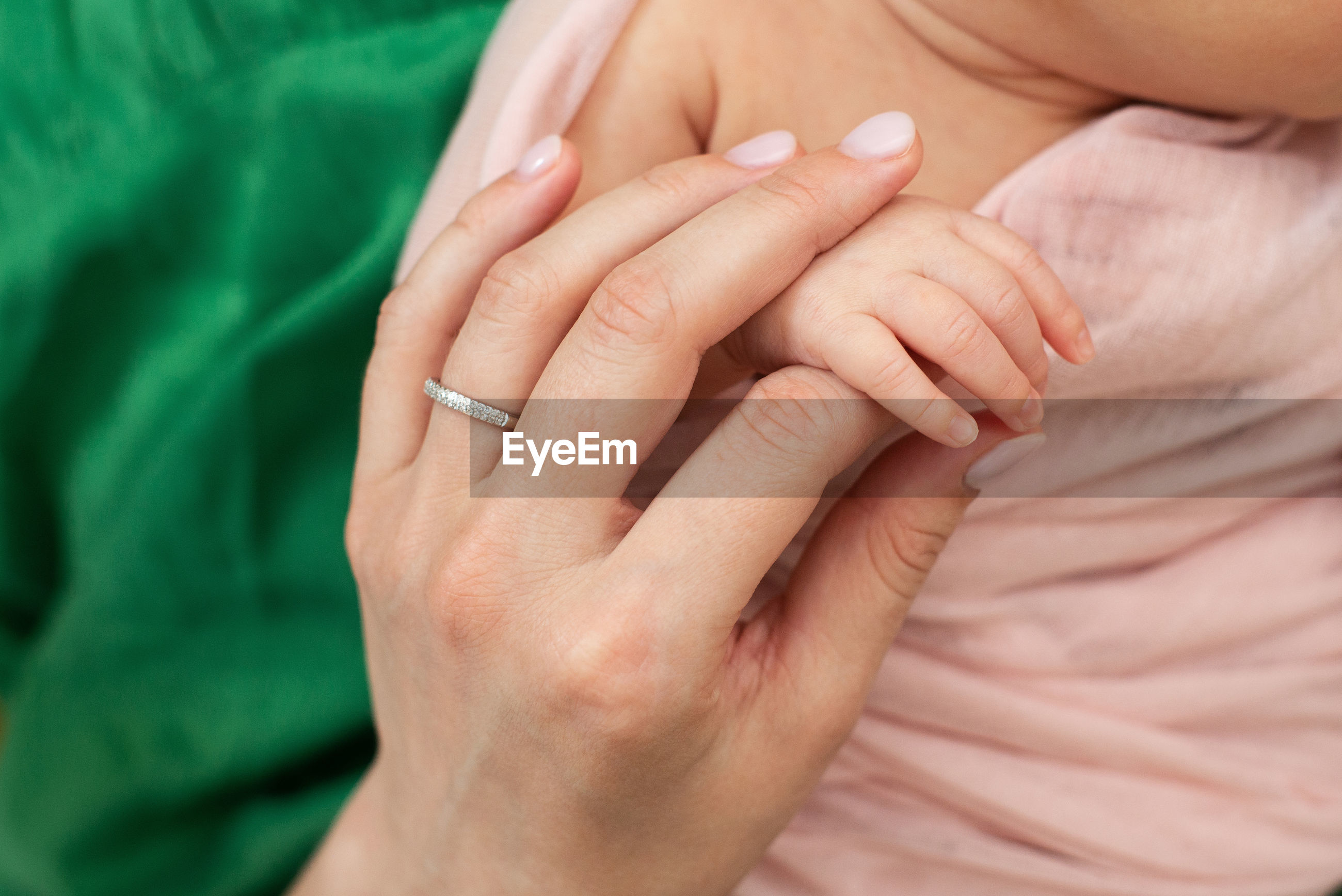Cropped hand of mother holding baby hand outdoors