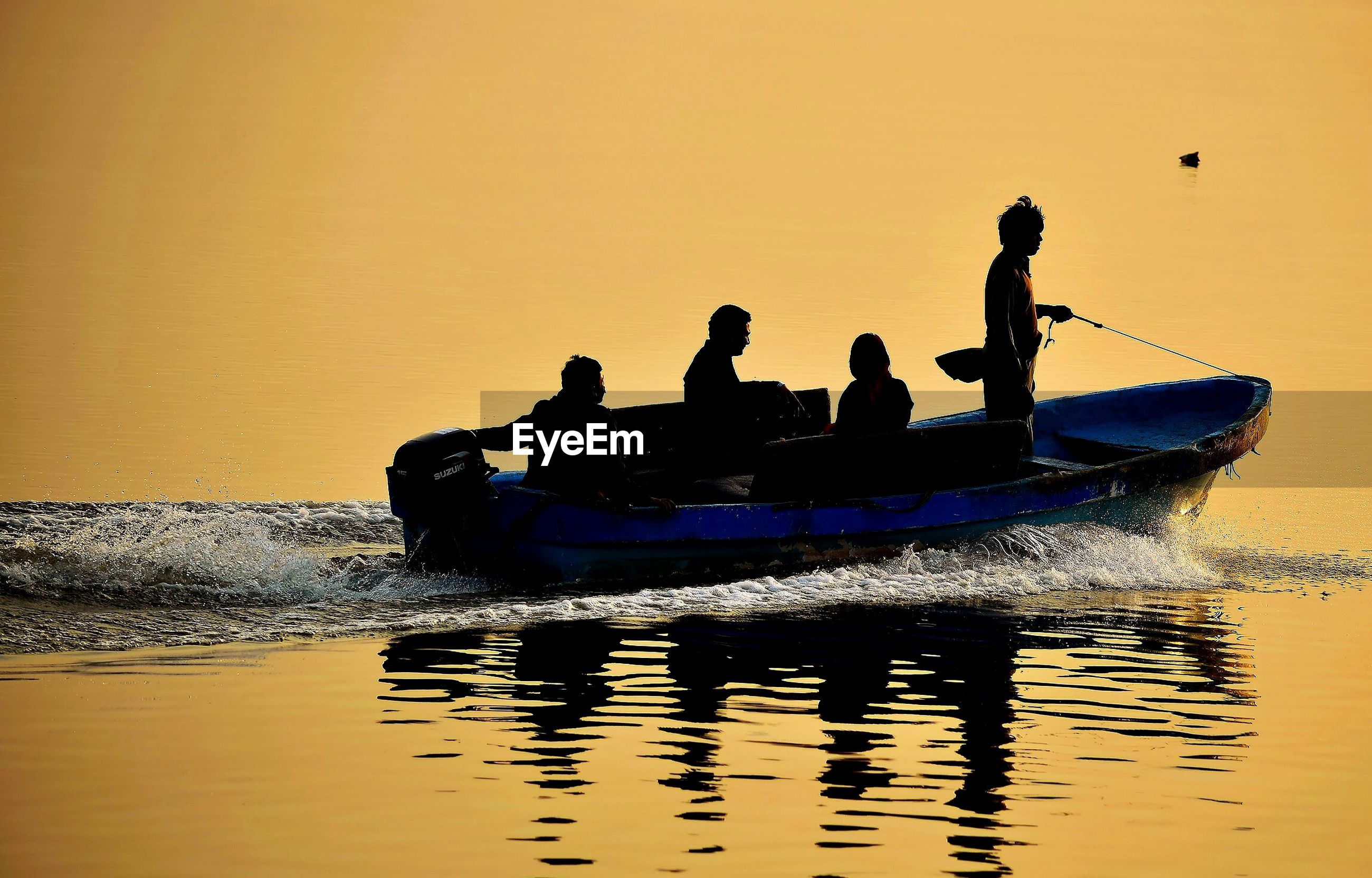 Silhouette people in little motor boat at sunset