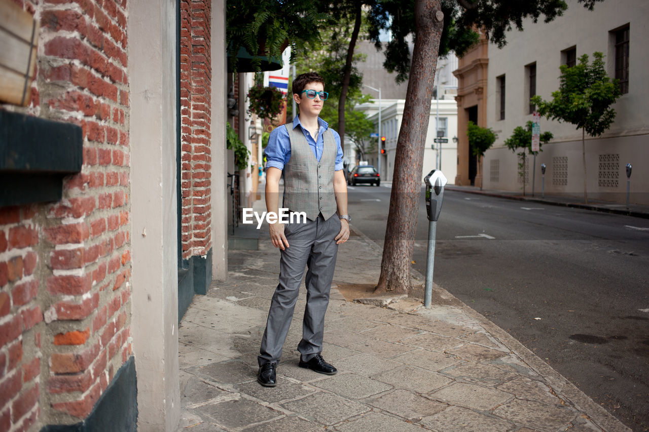 Full length of young man standing on sidewalk in city