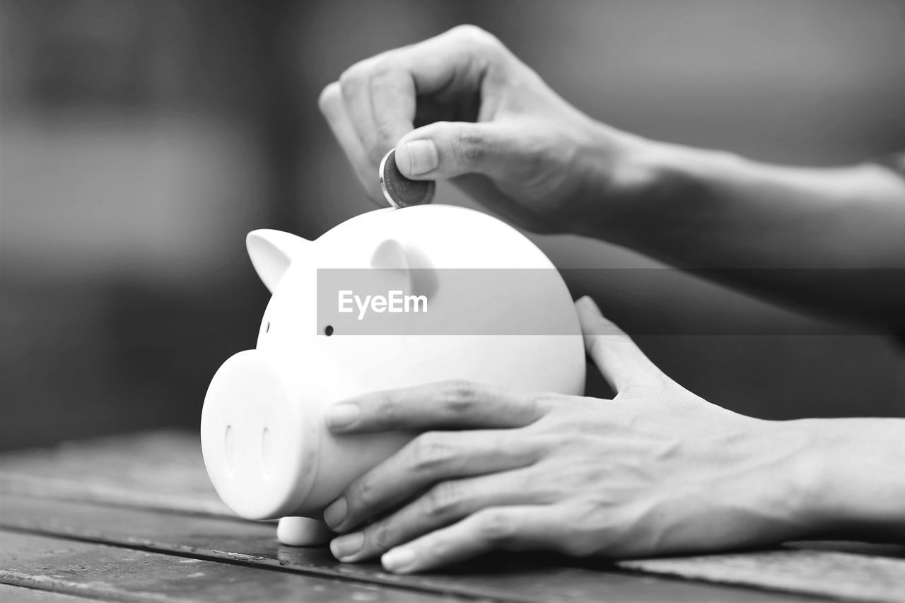 Cropped Hand Of Man Inserting Coin In Piggy Bank