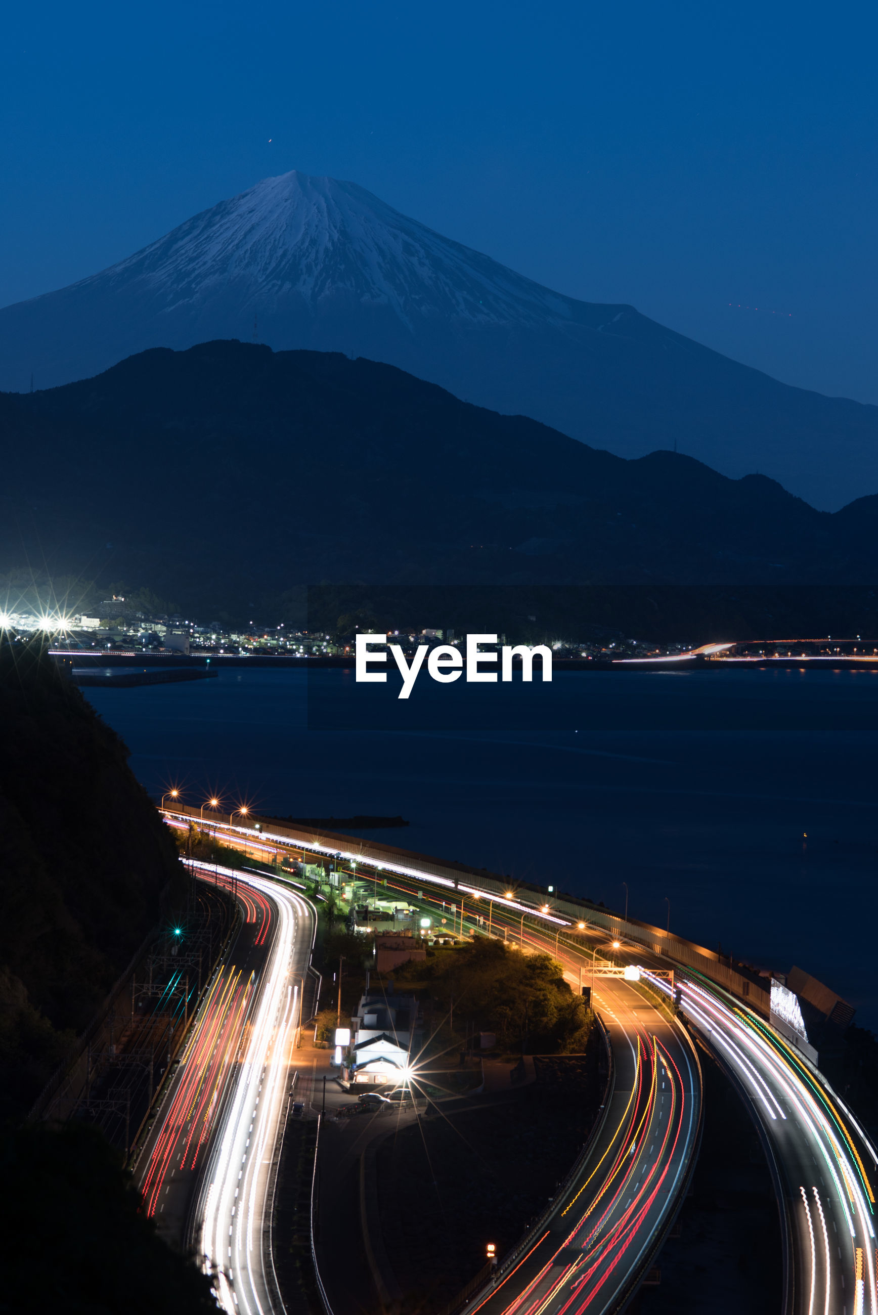 High angle view of light trails on road by mount fuji at night