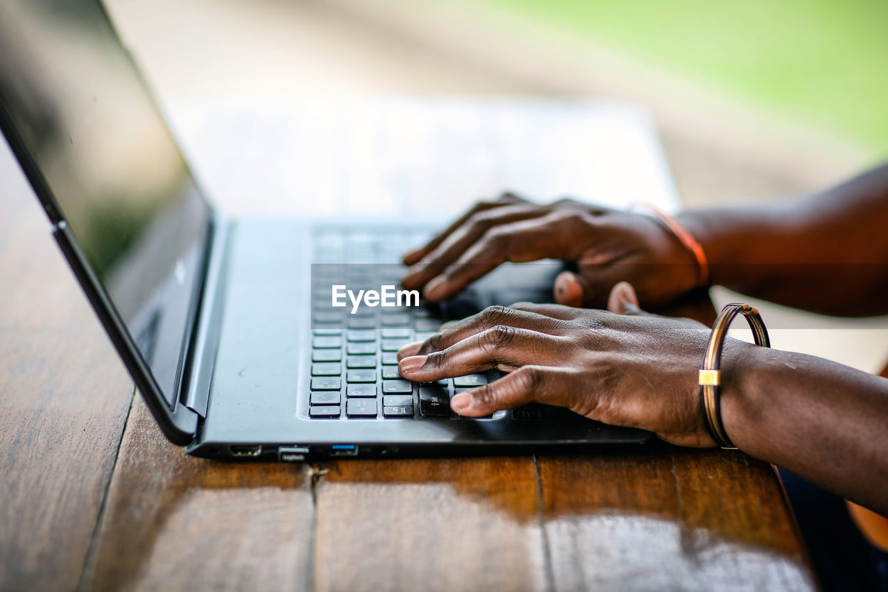 Cropped Hands Of Man Using Laptop On Wooden Table