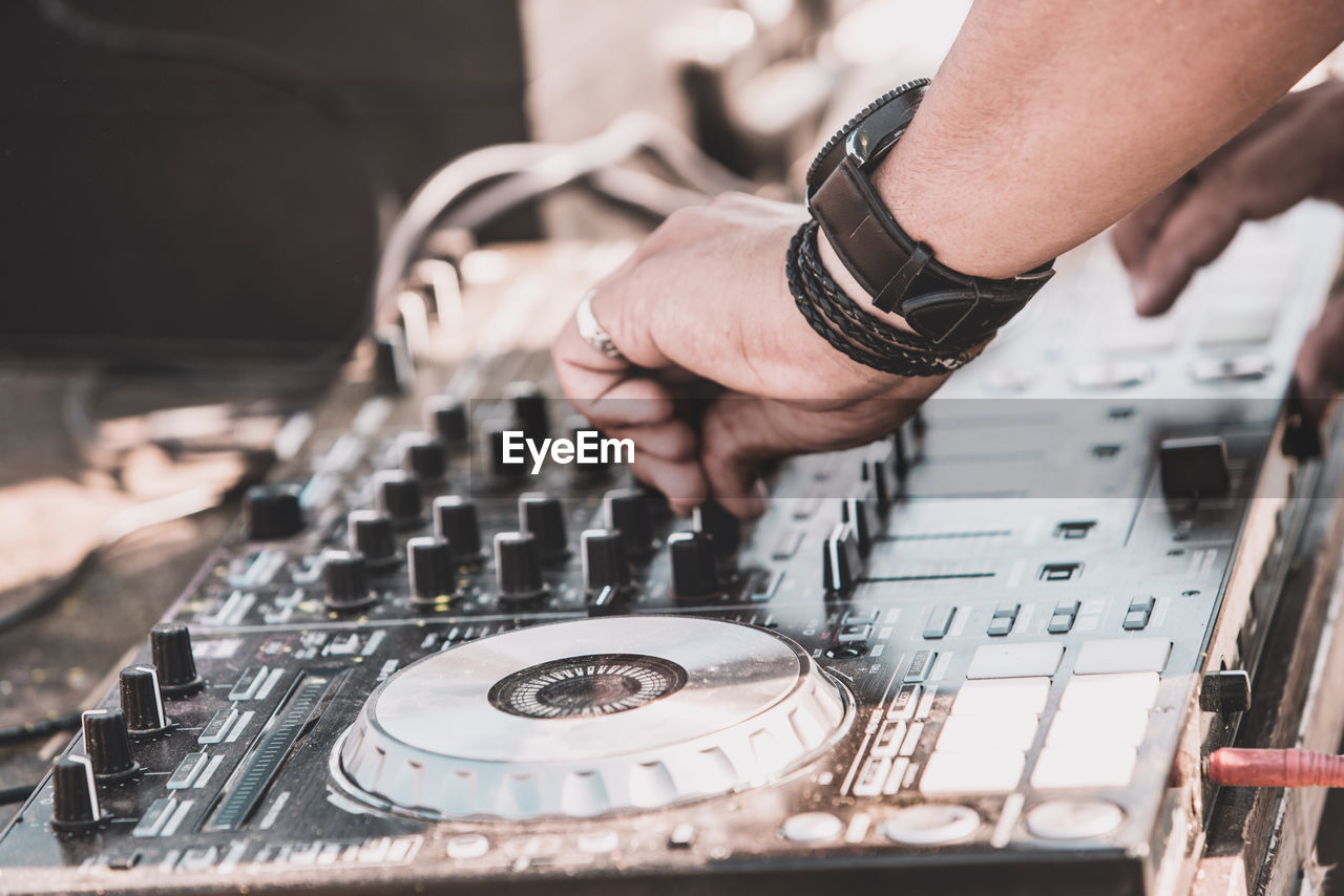human hand, hand, real people, music, one person, arts culture and entertainment, human body part, technology, men, indoors, selective focus, playing, record, skill, musical instrument, body part, turntable, focus on foreground, musical equipment, finger, nightlife