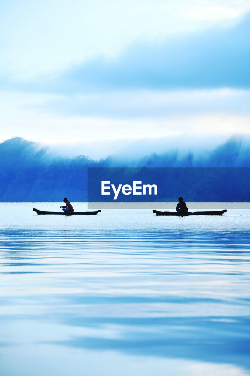 nautical vessel, water, mode of transportation, waterfront, transportation, beauty in nature, cloud - sky, scenics - nature, sky, day, nature, real people, sea, two people, tranquil scene, men, tranquility, travel, outdoors, paddling